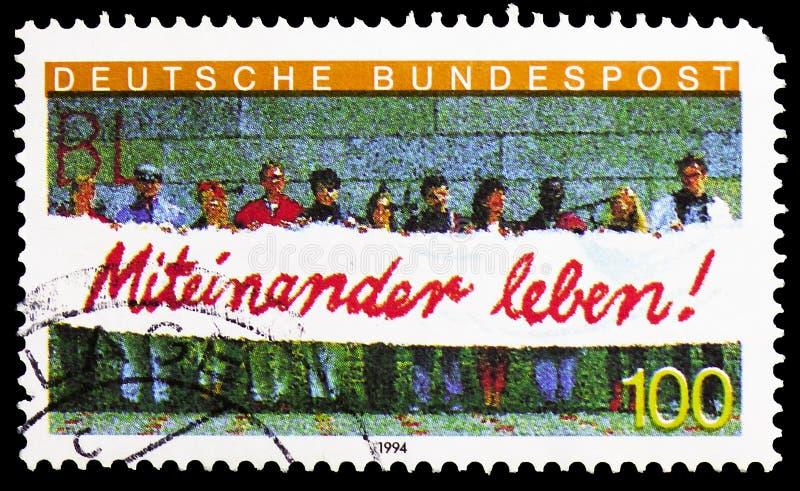 """La gente che tiene insegna, """"vivendo insieme """"integrazione dei lavoratori stranieri nel serie della Germania, circa 1994 fotografie stock"""
