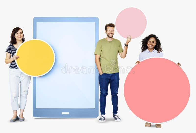 La gente che tiene le icone geometriche davanti ad un ritaglio di carta di una compressa fotografie stock libere da diritti