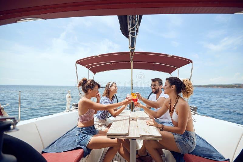 La gente che tosta le bevande sulla piattaforma e sulla risata dell'yacht Uomini allegri e donna che fanno festa su una barca fotografie stock libere da diritti