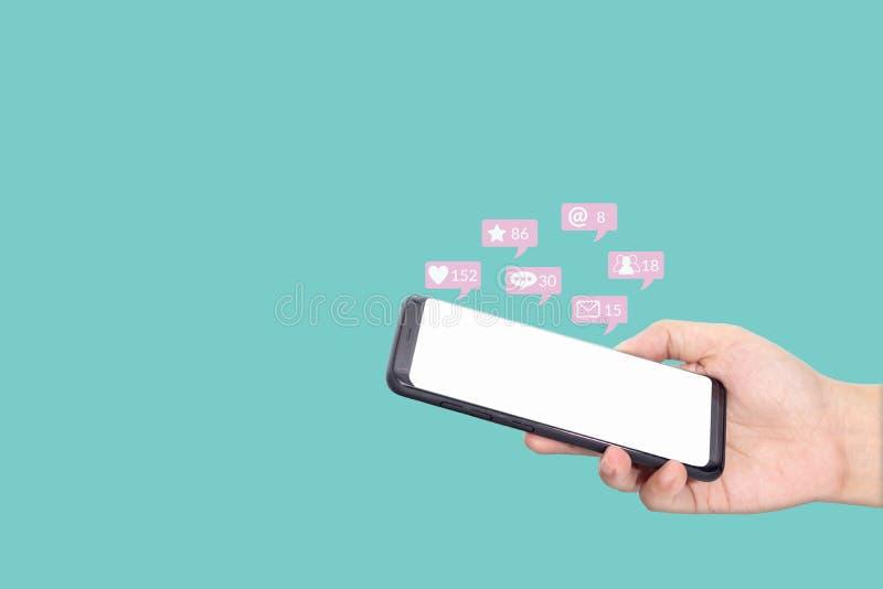 La gente che utilizza smartphone mobile con lo schermo bianco in bianco per le interazioni sociali di media con le icone di notif fotografie stock