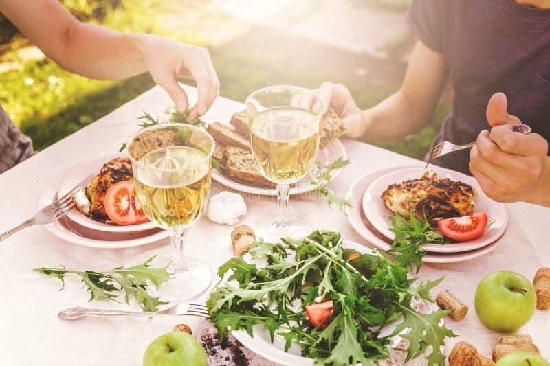 La gente come en el jardín en la tabla Concepto de la cena con el vino en el aire fresco Pescados y ensaladas con las verduras y  fotos de archivo