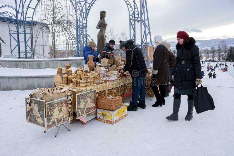 La gente compra i ricordi russi tradizionali dalla corteccia di betulla ad una fiera nel centro di Krasnojarsk durante il nuovo a immagine stock