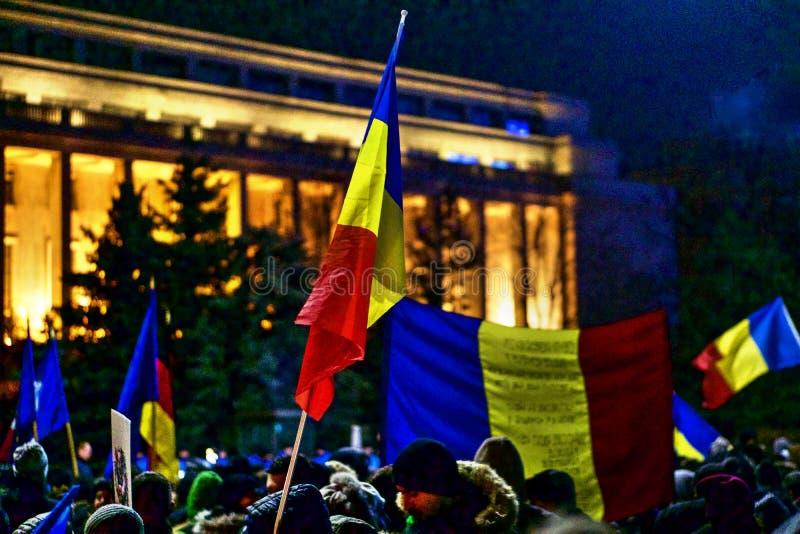 La gente con la bandiera rumena, protestante contro il governo corrotto immagini stock
