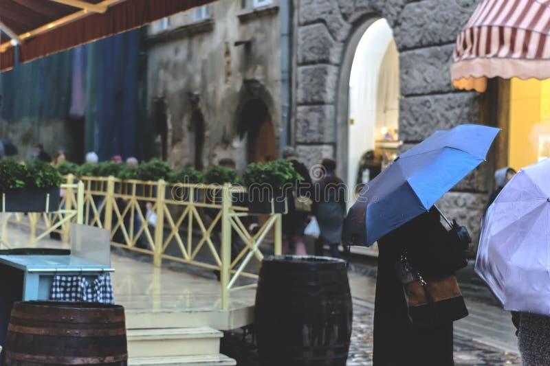 La gente con gli ombrelli nella pioggia nella vecchia città Profondità del campo poco profonda Fuoco sull'ombrello immagine stock