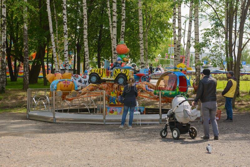 La gente con i bambini guida sul carosello nel parco fotografia stock