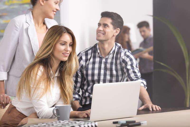 La gente con il computer portatile che gode del lavoro di squadra fotografie stock libere da diritti