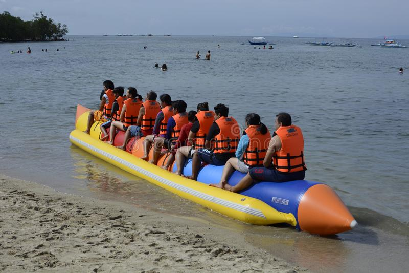 La gente con il giubbotto di salvataggio che ha giro di gioia sulla barca di banana lunga sulla spiaggia sabbiosa fotografia stock libera da diritti