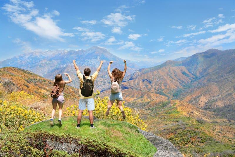 La gente con le mani su che saltano e che si divertono sulla cima della montagna fotografia stock