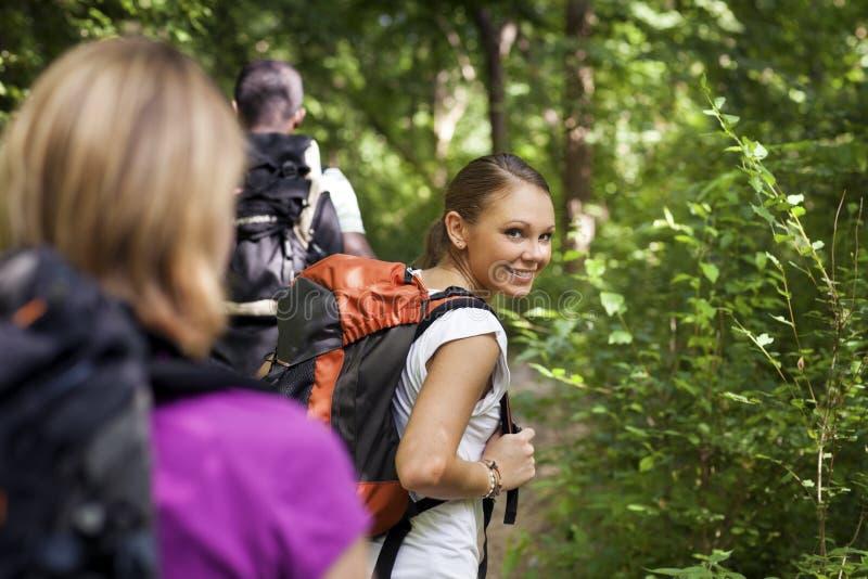 La gente con lo zaino che fa trekking in legno immagine stock