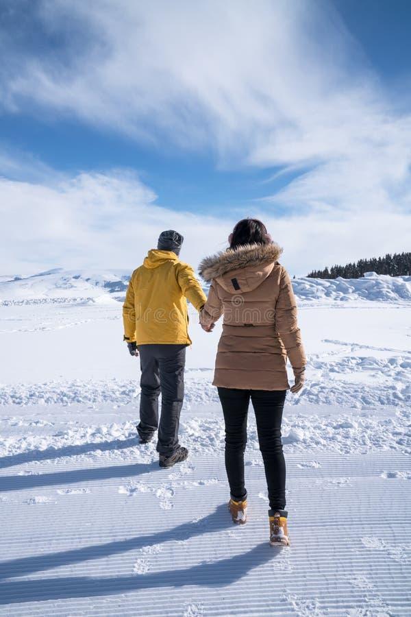La gente, concetto di stagione - coppia felice camminante all'aperto nell'inverno immagine stock