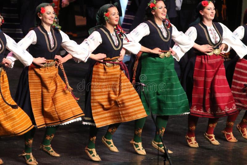 La gente in costumi tradizionali di folclore esegue la danza popolare Horo bulgaro fotografie stock libere da diritti