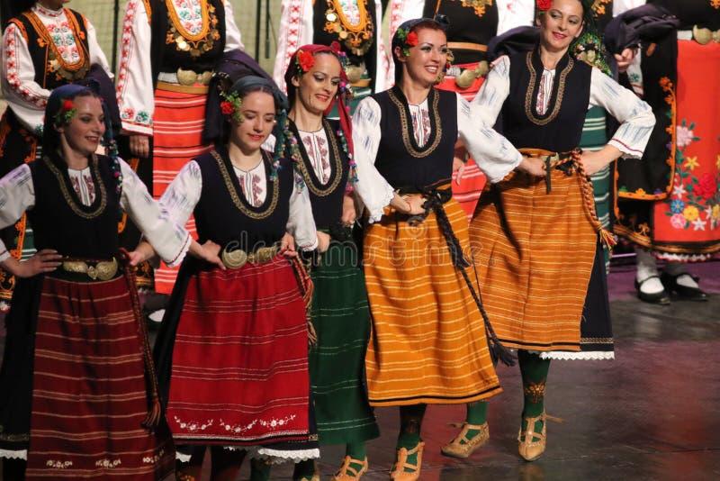 La gente in costumi tradizionali di folclore esegue la danza popolare Horo bulgaro fotografie stock
