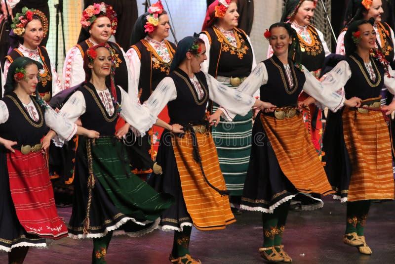 La gente in costumi tradizionali di folclore esegue la danza popolare Horo bulgaro immagini stock libere da diritti