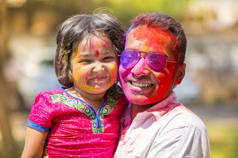 La gente cubierta en polvo colorido teñe la celebración del festival hindú de Holi en Dhakah en Bangladesh fotografía de archivo