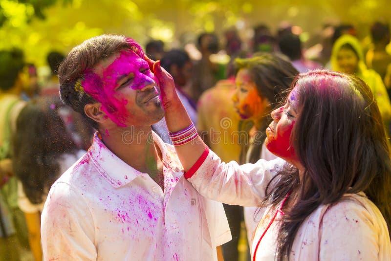 La gente cubierta en polvo colorido teñe la celebración del festival hindú de Holi en Dhakah en Bangladesh fotos de archivo