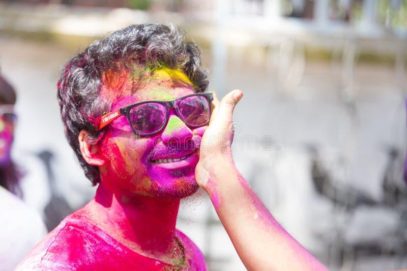 La gente cubierta en polvo colorido teñe la celebración del festival hindú de Holi en Dhakah en Bangladesh foto de archivo
