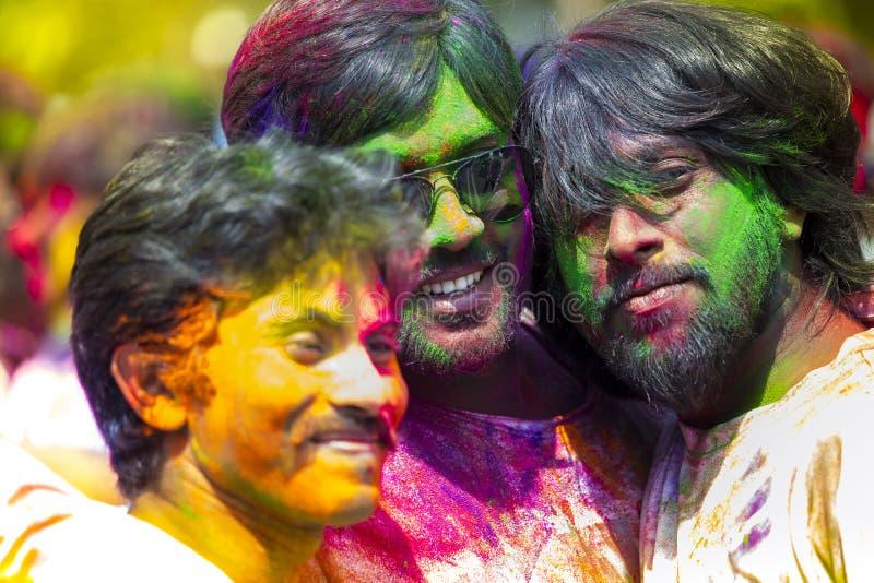 La gente cubierta en polvo colorido teñe la celebración del festival hindú de Holi en Dhakah en Bangladesh imagen de archivo