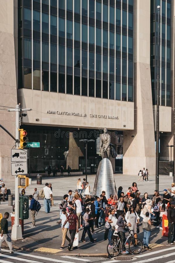 La gente dalla statua di Adam Clayton Powell Jr in Harlem, New York, U.S.A. immagini stock