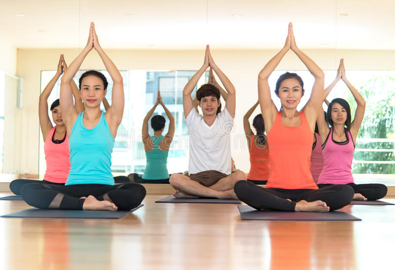 La gente de Asia que practica y que ejercita vital medita yoga en clase imagenes de archivo