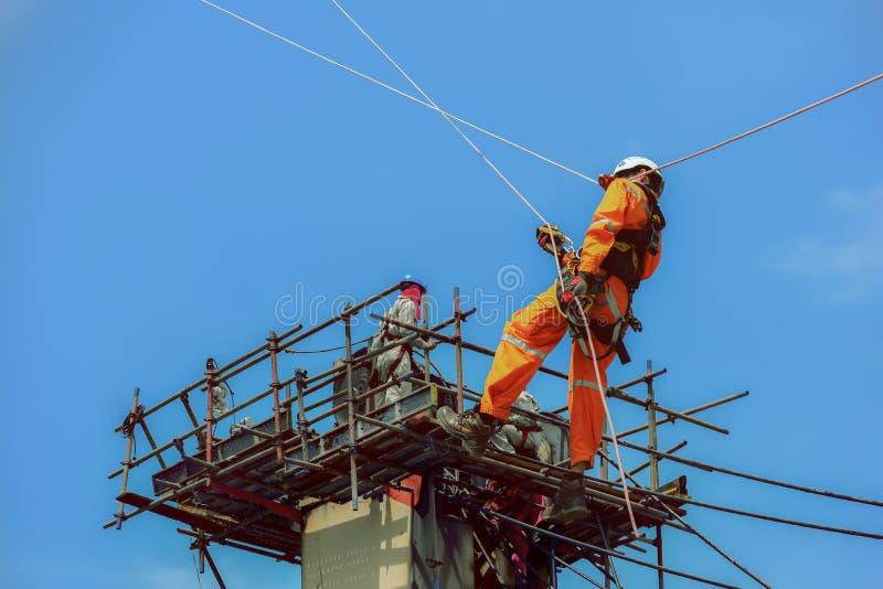 La gente de los trabajadores y el hombre de la seguridad asperjan encima de alto imágenes de archivo libres de regalías