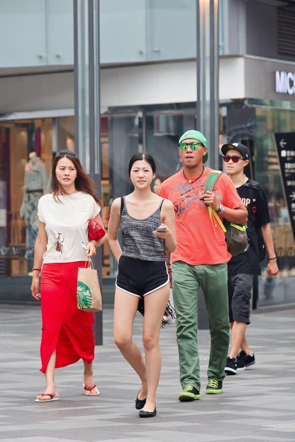 La gente de moda camina en el área de compras del pueblo, Pekín, China foto de archivo