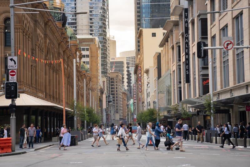 La gente de Sydney en ciudad cruzó la calle durante después de hora de trabajo en área comercial imagen de archivo libre de regalías