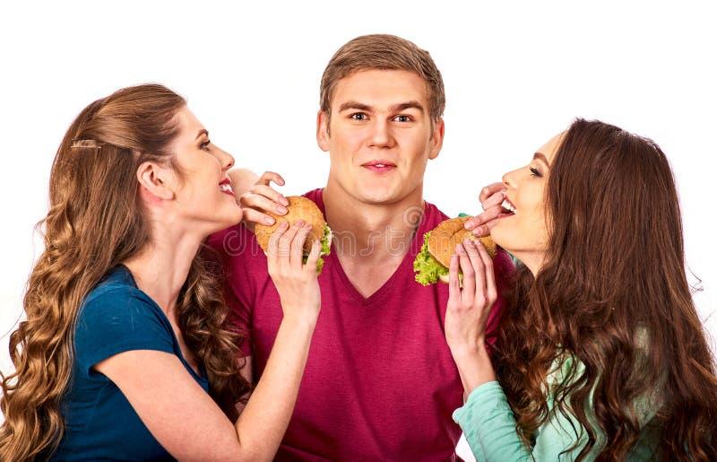 La gente del grupo come la hamburguesa Las mujeres y el hombre toman los alimentos de preparación rápida fotos de archivo