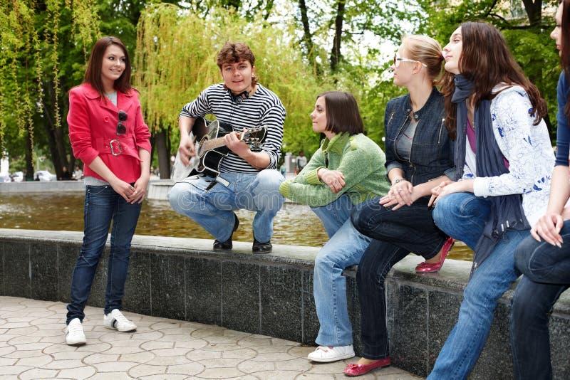 La gente del grupo con la guitarra en parque de la ciudad escucha música foto de archivo