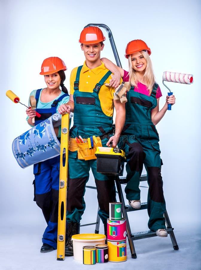 La gente del gruppo del costruttore con gli strumenti for Piani di costruzione del costruttore