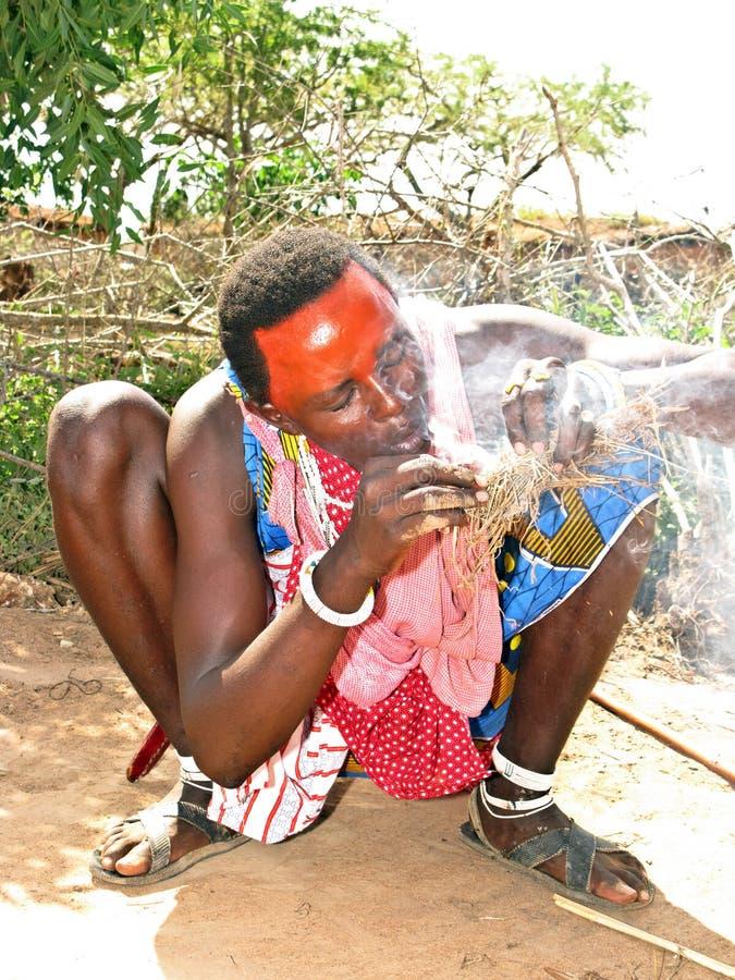 La gente del Masai che fa fuoco con paglia immagine stock libera da diritti