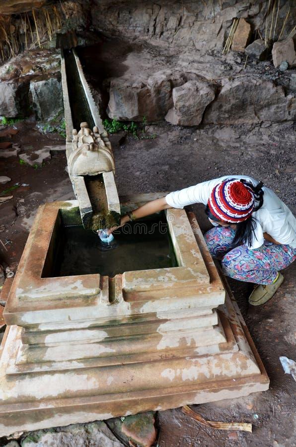 La gente del viaggiatore riempie lo scorrimento dell'acqua santo o benedetto dalla montagna di pietra fotografia stock