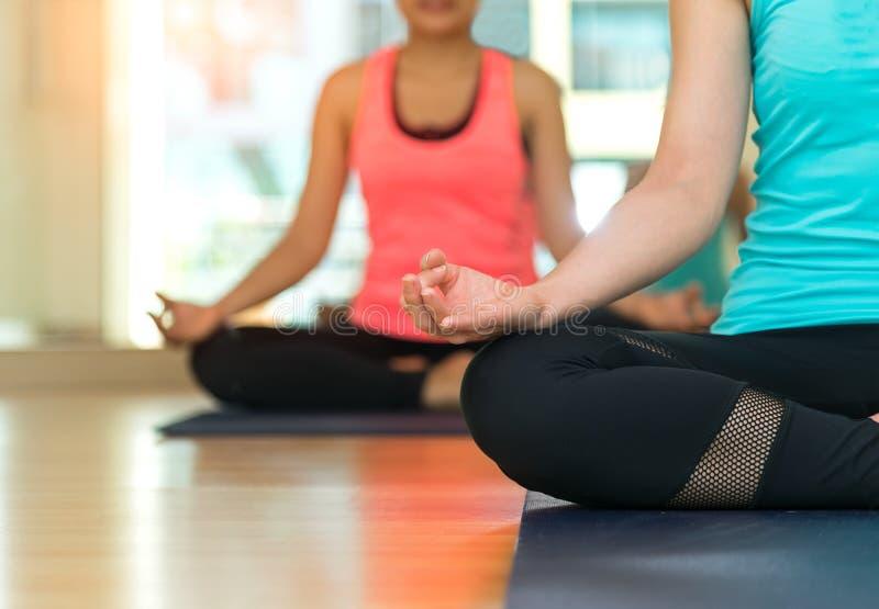 La gente dell'Asia che pratica e che si esercita vitale medita l'yoga nella classe fotografie stock