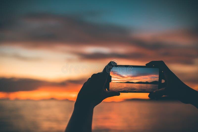 La gente della siluetta utilizza il telefono cellulare prende una vista sul mare con il tramonto immagini stock libere da diritti