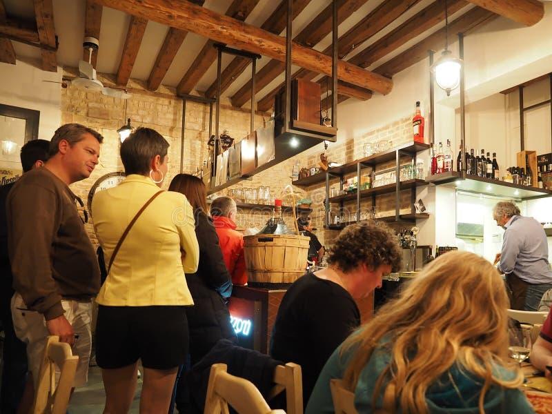 La gente dentro pizzeria con le bevande in Italia immagine stock libera da diritti