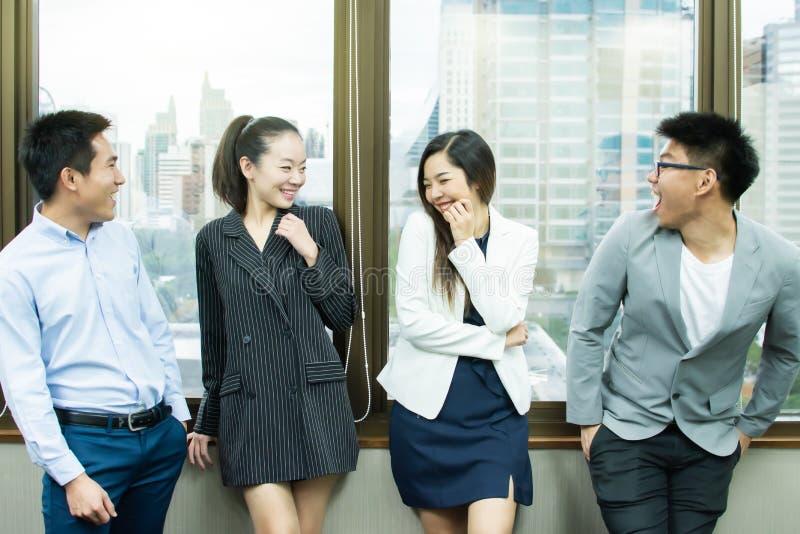La gente di affari è ridente e stante accanto alla finestra fotografie stock libere da diritti