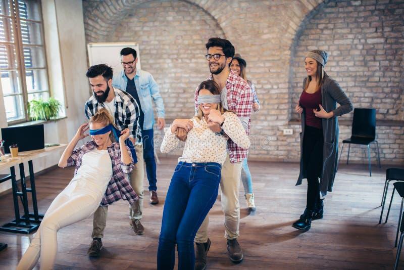 La gente di affari che fa l'esercizio di allenamento del gruppo durante il seminario di team-building, gioca della fiducia fotografie stock