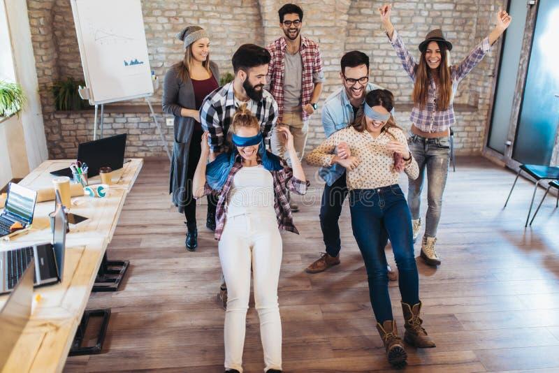 La gente di affari che fa l'esercizio di allenamento del gruppo durante il team-building gioca della fiducia fotografia stock