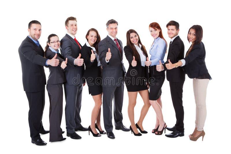 La gente di affari che mostra i pollici aumenta il segno fotografia stock