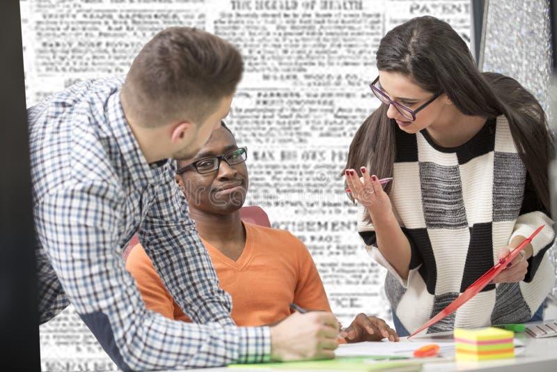 La gente di affari contemporanea multirazziale di lavoro si è collegata con i dispositivi tecnologici come la compressa ed il com fotografia stock