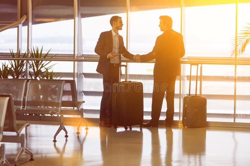 La gente di affari dà la stretta di mano all'aeroporto immagine stock