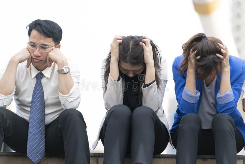 La gente di affari disoccupata dalla società si siede sulla via immagini stock