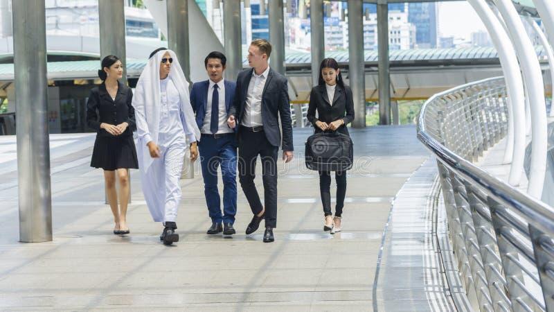 La gente di affari globale dell'uomo e donna astuti cammina e parla l'affare fotografie stock libere da diritti