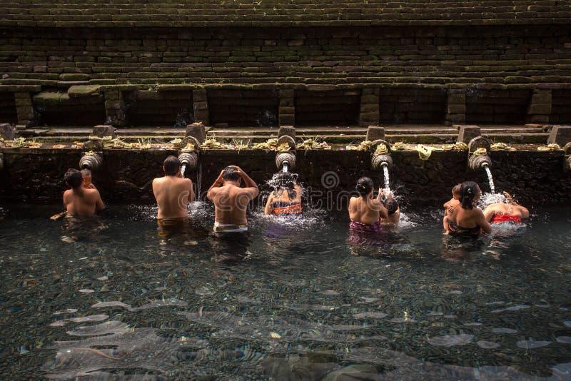 La gente di balinese che lava in acqua sorgiva santa nello stagno sacro a Pura Tirta Empul Temple fotografie stock libere da diritti