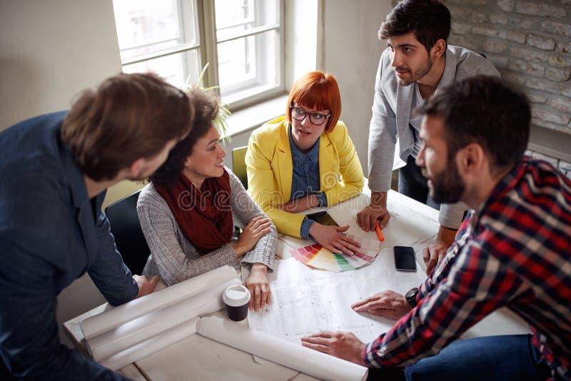 La gente di lavoro di squadra degli architetti dello studente con l'uomo del capo alla riunione immagine stock
