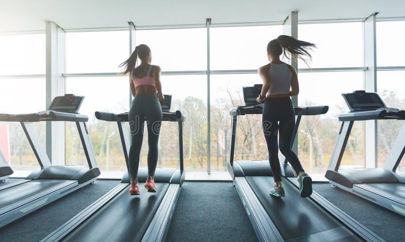 La gente di sport che corre sulle pedane mobili, guardanti fuori la finestra fotografie stock