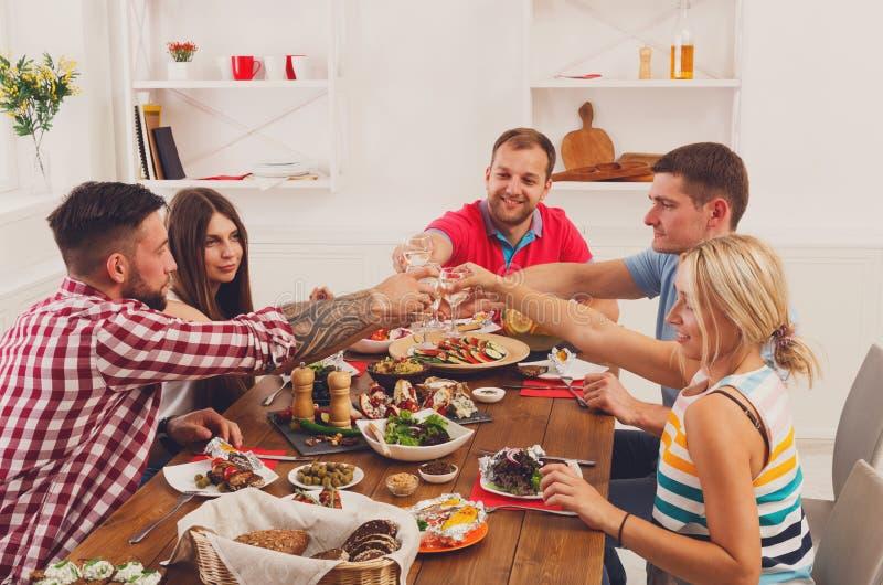 La gente dice i vetri del tintinnio di acclamazioni al partito di cena festivo della tavola immagini stock libere da diritti