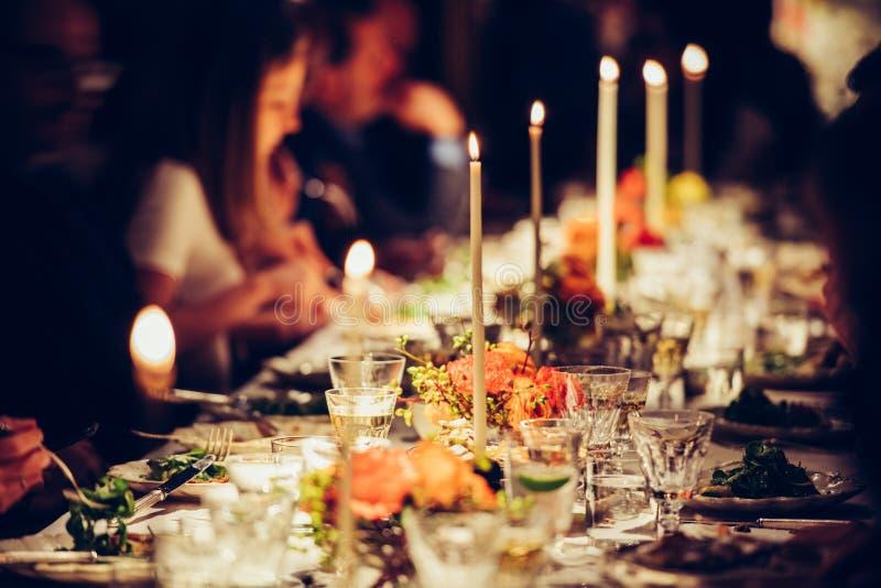 La gente disfruta de una cena de la familia con las velas Tabla grande servida con la comida y las bebidas foto de archivo