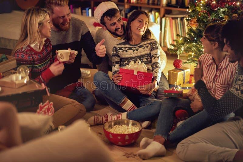 La gente divertida está compartiendo los regalos con decoraciones de la Navidad y un árbol de navidad hermoso Concepto de la Navi foto de archivo