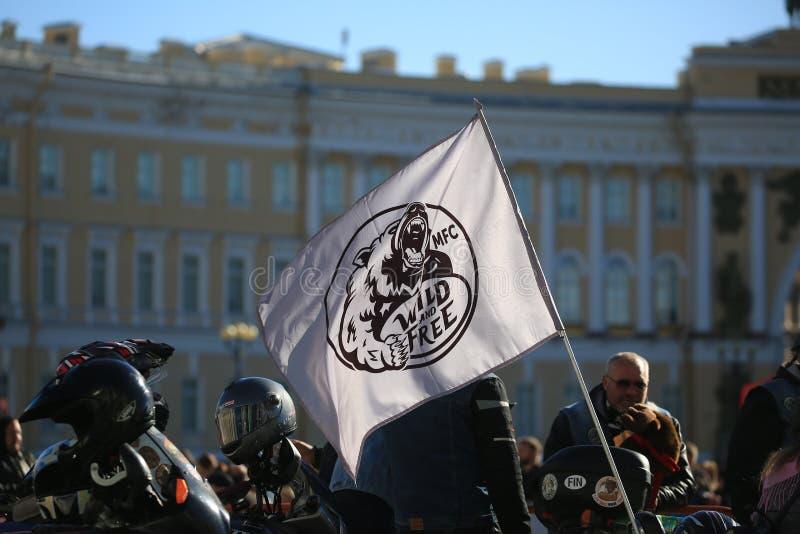 La gente e bandiera del club selvaggio e libero dei fanats di moto contro lo sfondo della costruzione dello stato maggiore fotografie stock libere da diritti