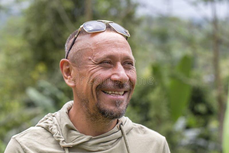 La gente e concetto di stile di vita Uomo non rasato di mezza età felice con il sorriso allegro all'aperto contro il fondo verde  fotografia stock libera da diritti